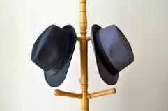 Κινηματογράφηση σε πρώτο πλάνο ενός μαύρου καπέλου και ενός γκρίζου καπέλου σε μια κρεμάστρα Στοκ εικόνα με δικαίωμα ελεύθερης χρήσης