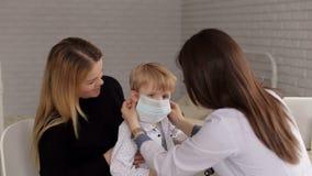 Κινηματογράφηση σε πρώτο πλάνο ενός μικρού αγοριού σε μια ιατρική μάσκα σε μια υποδοχή στον παιδίατρο απόθεμα βίντεο