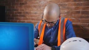 Κινηματογράφηση σε πρώτο πλάνο ενός νέου αρχιτέκτονα που φορούν μια γενειάδα και τα γυαλιά και των εργασιών για ένα lap-top πέρα  απόθεμα βίντεο