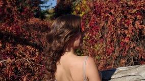 Κινηματογράφηση σε πρώτο πλάνο ενός νέου κοριτσιού σε ένα όμορφο φόρεμα βραδιού που περπατά στο πάρκο φθινοπώρου φιλμ μικρού μήκους