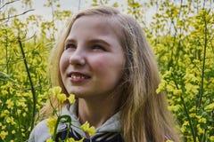 Κινηματογράφηση σε πρώτο πλάνο ενός νέου κοριτσιού ευτυχούς μια ηλιόλουστη ημέρα σε έναν τομέα συναπόσπορων στοκ φωτογραφία με δικαίωμα ελεύθερης χρήσης