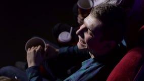 Κινηματογράφηση σε πρώτο πλάνο ενός νεαρού άνδρα που τρώει popcorn σε μια κινηματογραφική αίθουσα απόθεμα βίντεο