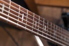 Κινηματογράφηση σε πρώτο πλάνο ενός ξύλινου καφετιού λαιμού και των σειρών κιθάρων Κατάστημα έννοιας των μουσικών οργάνων, συναυλ στοκ εικόνα