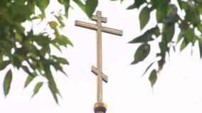 Κινηματογράφηση σε πρώτο πλάνο ενός ορθόδοξου σταυρού σε μια εκκλησία μέσω των πράσινων φύλλων ενάντια σε έναν άσπρο ουρανό απόθεμα βίντεο