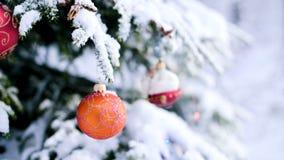 Κινηματογράφηση σε πρώτο πλάνο ενός παιχνιδιού Χριστουγέννων σε ένα χιονισμένο ζωηρό δέντρο στο χειμερινό δάσος στο υπόβαθρο των  φιλμ μικρού μήκους