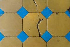 Κινηματογράφηση σε πρώτο πλάνο ενός παλαιού κεραμιδιού πατωμάτων με ένα δίχρωμο σχέδιο Προκαλεσμένα σκασίματα κεραμίδια πατωμάτων Στοκ Φωτογραφία