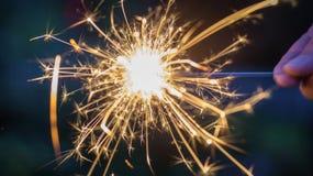 Κινηματογράφηση σε πρώτο πλάνο ενός προσώπου που κρατά ένα sparkler τη νύχτα Στοκ Εικόνα