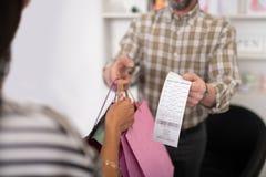 Κινηματογράφηση σε πρώτο πλάνο ενός πωλητή που παρέχει σε έναν πελάτη τις συσκευασίες αγορών στοκ φωτογραφία με δικαίωμα ελεύθερης χρήσης