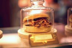 Κινηματογράφηση σε πρώτο πλάνο ενός σάντουιτς που εκτίθεται σε μια προθήκη και ένα θολωμένο υπόβαθρο Στοκ Εικόνα