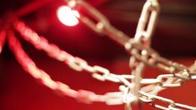 Κινηματογράφηση σε πρώτο πλάνο ενός συνόλου συμπεπλεγμένων αλυσίδων σε ένα φωτεινό κόκκινο υπόβαθρο απόθεμα βίντεο