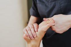 Κινηματογράφηση σε πρώτο πλάνο ενός φυσιοθεραπευτή που δίνει την άσκηση στο πόδι ατόμων ` s στοκ εικόνες