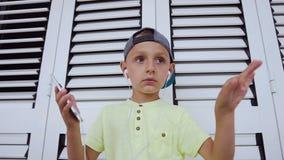 Κινηματογράφηση σε πρώτο πλάνο ενός χαριτωμένου αγοριού στην μπλούζα και την ΚΑΠ που ακούει τη μουσική στα ακουστικά από το γκρίζ απόθεμα βίντεο