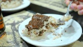 Κινηματογράφηση σε πρώτο πλάνο ενός χεριού γυναικών ` s με το κουτάλι που τρώει ένα κομμάτι από ένα σπιτικό κέικ με τα τσιπ σοκολ απόθεμα βίντεο