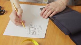 Κινηματογράφηση σε πρώτο πλάνο ενός χεριού γυναικών ` s, σκίτσα σχεδιαστών μόδας σχεδίων των ενδυμάτων στο ατελιέ απόθεμα βίντεο