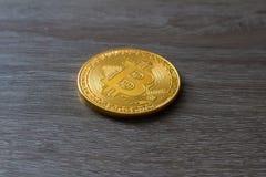 Κινηματογράφηση σε πρώτο πλάνο ενός χρυσού νομίσματος bitcoin στο ξύλινο υπόβαθρο Στοκ Φωτογραφία