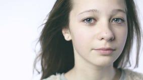 Κινηματογράφηση σε πρώτο πλάνο ενός όμορφου κοριτσιού εφήβων που εξετάζει τη κάμερα Η κάμερα κινείται αργά μετά από τα μεγάλα μπλ φιλμ μικρού μήκους