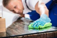 Κινηματογράφηση σε πρώτο πλάνο ενός Janitor καθαρίζοντας γραφείου με το ύφασμα Στοκ Φωτογραφία