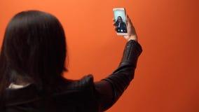 Κινηματογράφηση σε πρώτο πλάνο ενός selfie που πυροβολείται μιας νέας γυναίκας, σε ένα πορτοκαλί υπόβαθρο στο στούντιο φιλμ μικρού μήκους