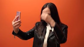 Κινηματογράφηση σε πρώτο πλάνο ενός selfie που πυροβολείται μιας νέας γυναίκας, σε ένα πορτοκαλί υπόβαθρο στο στούντιο απόθεμα βίντεο