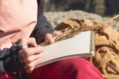 Κινηματογράφηση σε πρώτο πλάνο σε ετοιμότητα ενός κοριτσιού που κρατά ένα κενό σημειωματάριο Μια ξηρά ανθοδέσμη των χορταριών στο Στοκ φωτογραφίες με δικαίωμα ελεύθερης χρήσης
