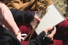 Κινηματογράφηση σε πρώτο πλάνο σε ετοιμότητα ενός κοριτσιού που κρατά ένα κενό σημειωματάριο Μια ξηρά ανθοδέσμη των χορταριών στο Στοκ Εικόνες