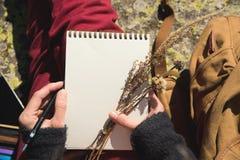 Κινηματογράφηση σε πρώτο πλάνο σε ετοιμότητα ενός κοριτσιού που κρατά ένα κενό σημειωματάριο Μια ξηρά ανθοδέσμη των χορταριών στο Στοκ Φωτογραφία