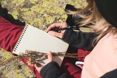 Κινηματογράφηση σε πρώτο πλάνο σε ετοιμότητα ενός κοριτσιού που κρατά ένα κενό σημειωματάριο Μια ξηρά ανθοδέσμη των χορταριών στο Στοκ φωτογραφία με δικαίωμα ελεύθερης χρήσης