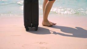 Κινηματογράφηση σε πρώτο πλάνο, θηλυκά γυμνά πόδια δίπλα σε μια βαλίτσα σε μια άσπρη παραλία θαλασσίως μικρό ταξίδι χαρτών του Δο στοκ εικόνες