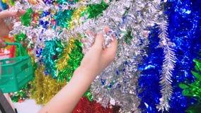Κινηματογράφηση σε πρώτο πλάνο, θηλυκά χέρια που αγοράζει τις διακοσμήσεις Χριστουγέννων Το κορίτσι επιλέγει tinsel Χριστουγέννων απόθεμα βίντεο