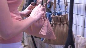 Κινηματογράφηση σε πρώτο πλάνο, θηλυκά χέρια το κορίτσι επιλέγει μια τσάντα στη λεωφόρο φιλμ μικρού μήκους
