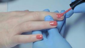 Κινηματογράφηση σε πρώτο πλάνο, κύρια μανικιούρ νύχια βερνικιών χρωμάτων κόκκινα σε ετοιμότητα του κοριτσιού φιλμ μικρού μήκους