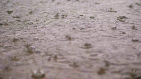 Κινηματογράφηση σε πρώτο πλάνο, μεγάλες, βαριές πτώσεις της βροχής, βροχοπτώσεις, ντους, πτώση με τους παφλασμούς νερού, φυσαλίδε φιλμ μικρού μήκους