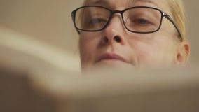 Κινηματογράφηση σε πρώτο πλάνο μιας γυναίκας που βγάζει φύλλα μέσω ενός βιβλίου Ξανθός με τα γυαλιά που διαβάζουν ένα βιβλίο απόθεμα βίντεο