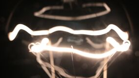 Κινηματογράφηση σε πρώτο πλάνο μιας κίτρινης σπείρας ενός λαμπτήρα ινών Ομαλό τρεμούλιασμα φιλμ μικρού μήκους