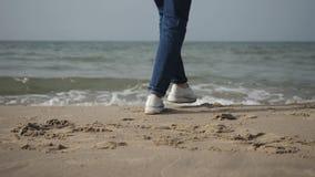 Κινηματογράφηση σε πρώτο πλάνο μιας νέας γυναίκας σε ένα μπεζ παλτό και το τζιν παντελόνι που χορεύουν στην παραλία της θάλασσας, απόθεμα βίντεο