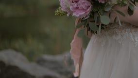 Κινηματογράφηση σε πρώτο πλάνο μιας όμορφης γαμήλιας ανθοδέσμης των λεπτών ρόδινων peonies στα χέρια της νύφης σε ένα γαμήλιο φόρ απόθεμα βίντεο