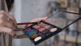 Κινηματογράφηση σε πρώτο πλάνο Μια παλέτα με τις σκιές ματιών και ένα makeup βουρτσίζουν στο makeup τα χέρια καλλιτεχνών ` s Το κ απόθεμα βίντεο