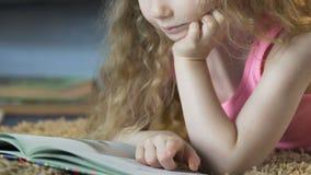 Κινηματογράφηση σε πρώτο πλάνο ξανθό να βρεθεί κοριτσιών στον τάπητα και της ανάγνωσης ενός βιβλίου, εκπαίδευση απόθεμα βίντεο