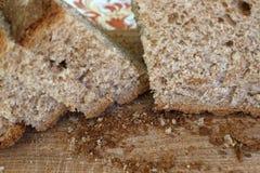 Κινηματογράφηση σε πρώτο πλάνο ολόκληρου του ψωμιού σιταριού που κόβεται breadboard Στοκ φωτογραφία με δικαίωμα ελεύθερης χρήσης