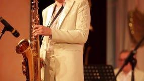 Κινηματογράφηση σε πρώτο πλάνο Ο μουσικός μιας ορχήστρας πνευστ0ών από χαλκό στα άσπρα παιχνίδια ενδυμάτων σόλο σε ένα saxophone- φιλμ μικρού μήκους