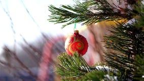 Κινηματογράφηση σε πρώτο πλάνο, παιχνίδια Χριστουγέννων που κρεμά σε έναν χιονισμένο κλάδο δέντρων χειμώνας, παγωμένη, χιονώδης,  απόθεμα βίντεο