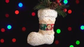 Κινηματογράφηση σε πρώτο πλάνο παιχνιδιών μποτών Χριστουγέννων Ντεκόρ με τα νέα φω'τα δέντρων έτους που αστράφτει στο υπόβαθρο φιλμ μικρού μήκους