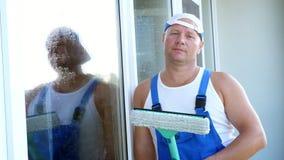 Κινηματογράφηση σε πρώτο πλάνο, πορτρέτο ενός άνδρα εργαζόμενος της καθαρίζοντας υπηρεσίας, στις μπλε φόρμες και σε μια ΚΑΠ, blas απόθεμα βίντεο