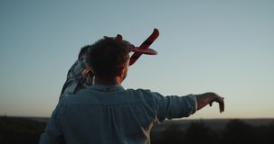 Κινηματογράφηση σε πρώτο πλάνο που αγκαλιάζει τον μπαμπά με το γιο του, και που κρατά ένα μεγάλο ηλιοβασίλεμα προσοχής αεροπλάνων απόθεμα βίντεο