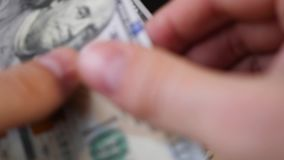 Κινηματογράφηση σε πρώτο πλάνο που μετατρέπει τους λογαριασμούς εκατό δολαρίων με το χέρι πρώτο βίντεο προσώπων φιλμ μικρού μήκους