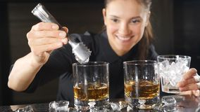 Κινηματογράφηση σε πρώτο πλάνο που πυροβολείται θηλυκό bartender που βάζει τον πάγο στο οινοπνευματώδες ποτό σε σε αργή κίνηση τα φιλμ μικρού μήκους