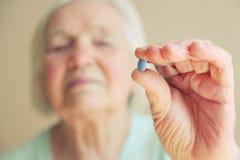 Κινηματογράφηση σε πρώτο πλάνο που πυροβολείται μιας ανώτερης γυναίκας που παρουσιάζει μπλε χάπι Έννοια ηλικιωμένου ανθρώπου υγει Στοκ Εικόνες