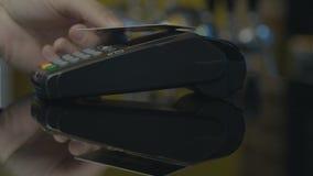 Κινηματογράφηση σε πρώτο πλάνο που πυροβολείται του προσώπου που χρησιμοποιεί την κινητή πληρωμή PayPass απόθεμα βίντεο