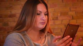 Κινηματογράφηση σε πρώτο πλάνο που πυροβολείται του υπέρβαρου μακρυμάλλους θηλυκού freelancer που εργάζεται ήρεμα με το smartphon φιλμ μικρού μήκους