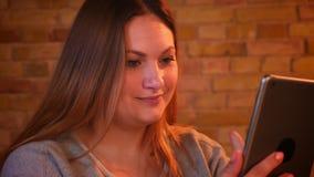 Κινηματογράφηση σε πρώτο πλάνο που πυροβολείται του υπέρβαρου μακρυμάλλους θηλυκού freelancer που εργάζεται προσεκτικά με το τηλέ φιλμ μικρού μήκους